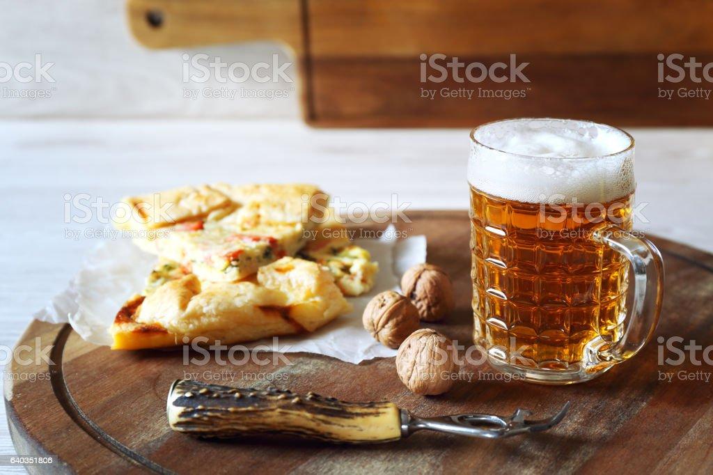 Mug of beer and zucchini and salmon pie stock photo