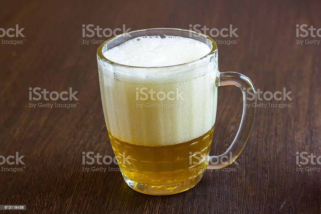 Mug of beer on wooden background stock photo