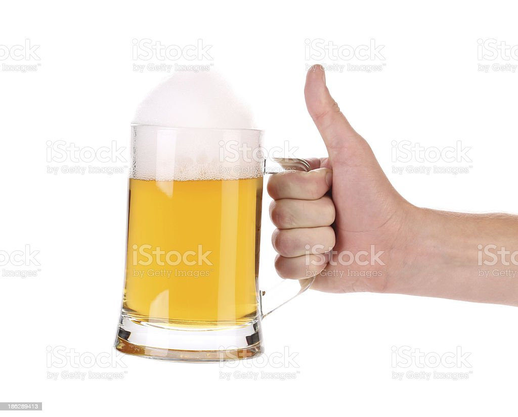 Mug of beer with foam in hand. royalty-free stock photo