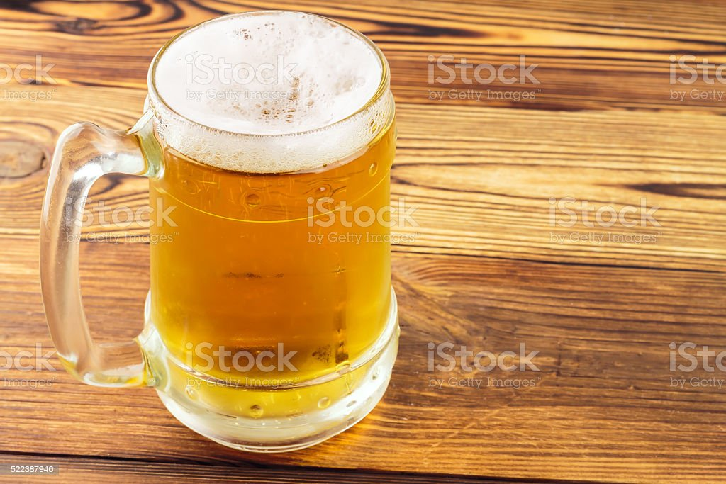 Mug of cold beer on wooden table stock photo