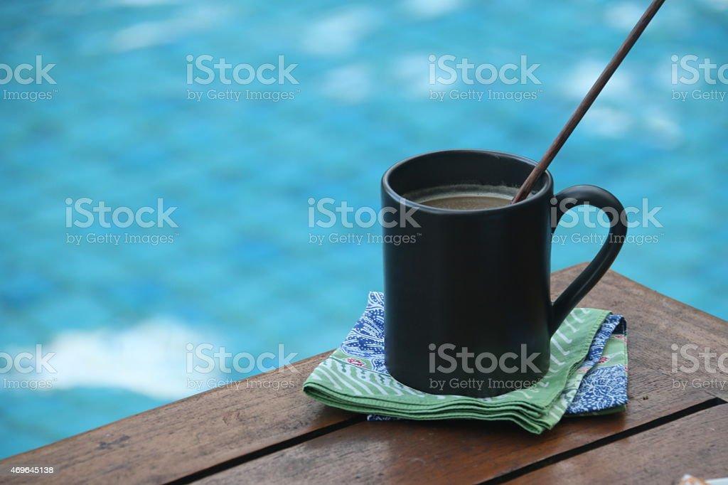 Mug of Creamy Coffee by the Blue Pool stock photo