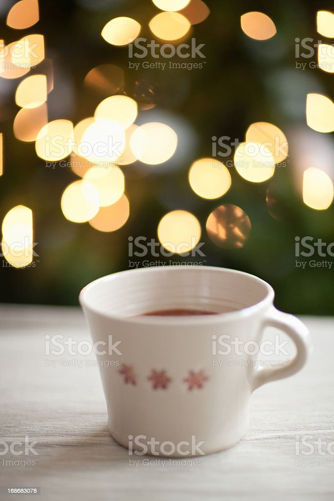 Mug of hot cocoa, Christmas tree in background royalty-free stock photo