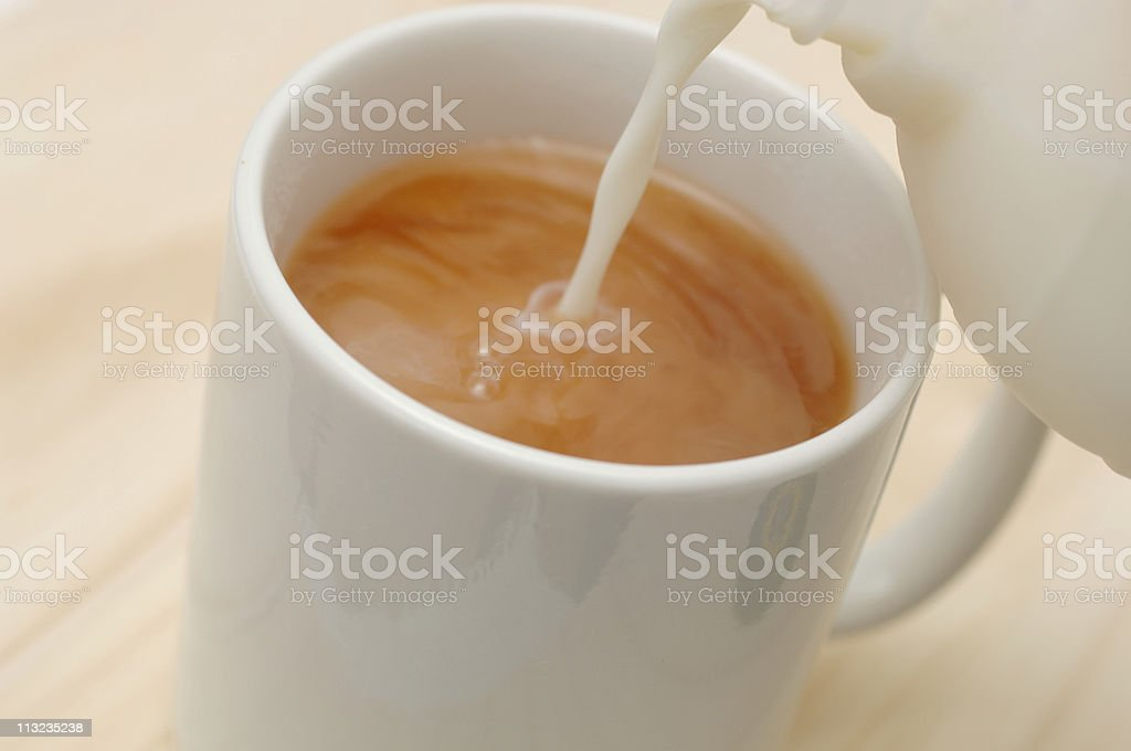 Mug of tea, coffee with milk pouring in stock photo