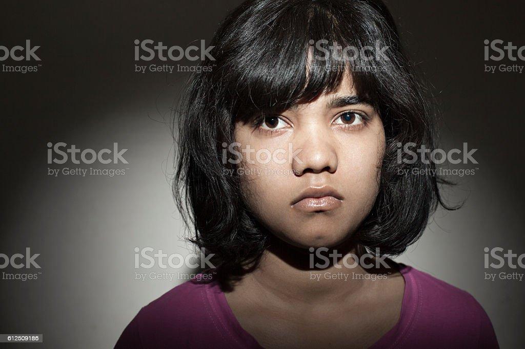 Mug shot of an unhappy teenage girl looking at camera. stock photo