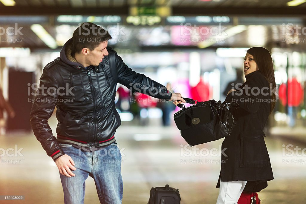Mugger trying to snatch purse from a young woman stock photo