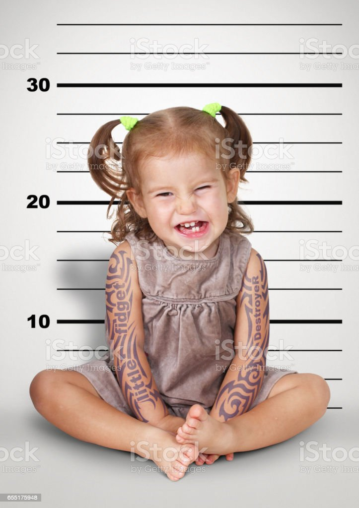 Mugshot, funny naughty baby with tattoo, disobedient child concept. stock photo