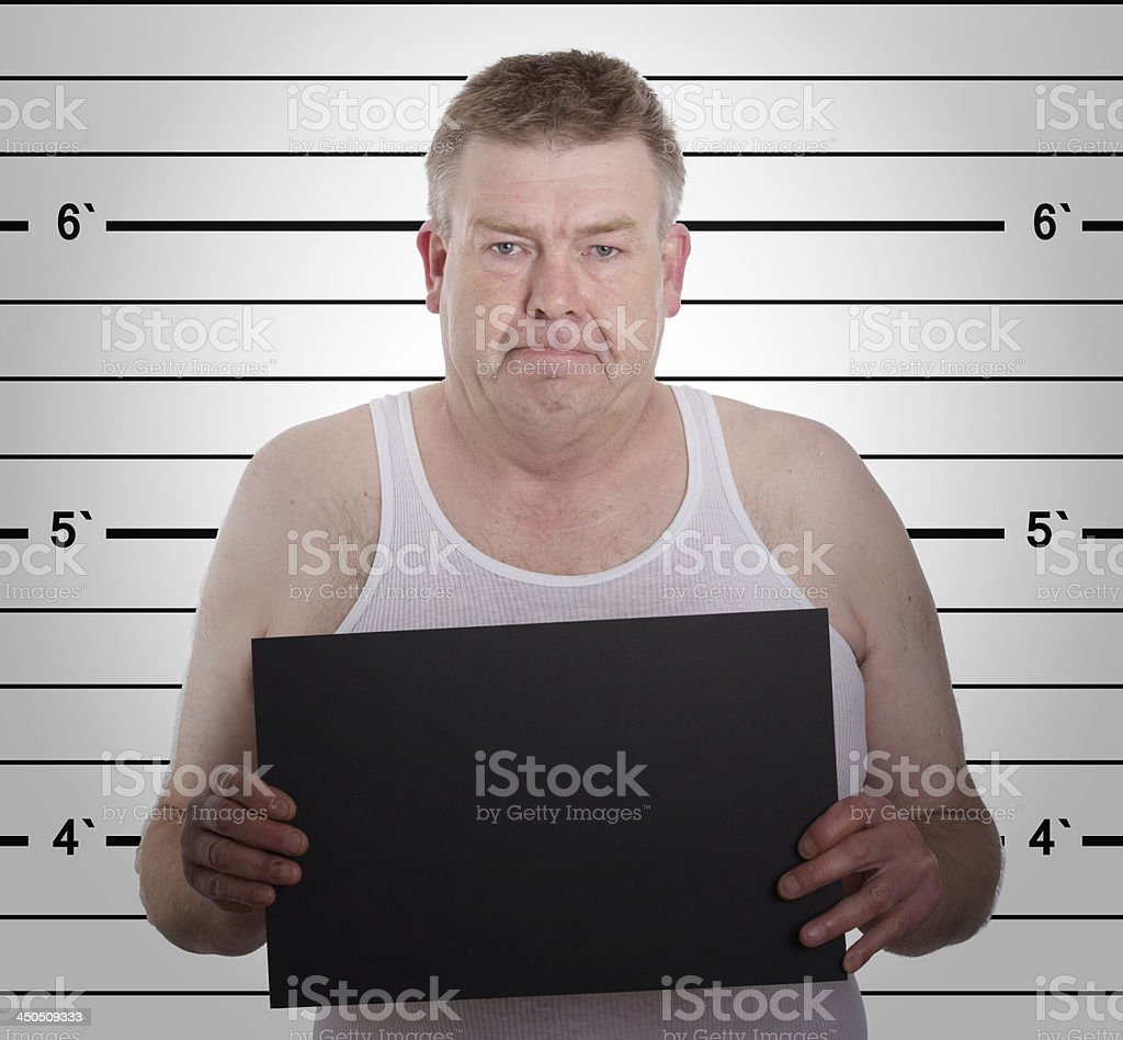 mugshot - young man arrested and  holding a  blackboard royalty-free stock photo