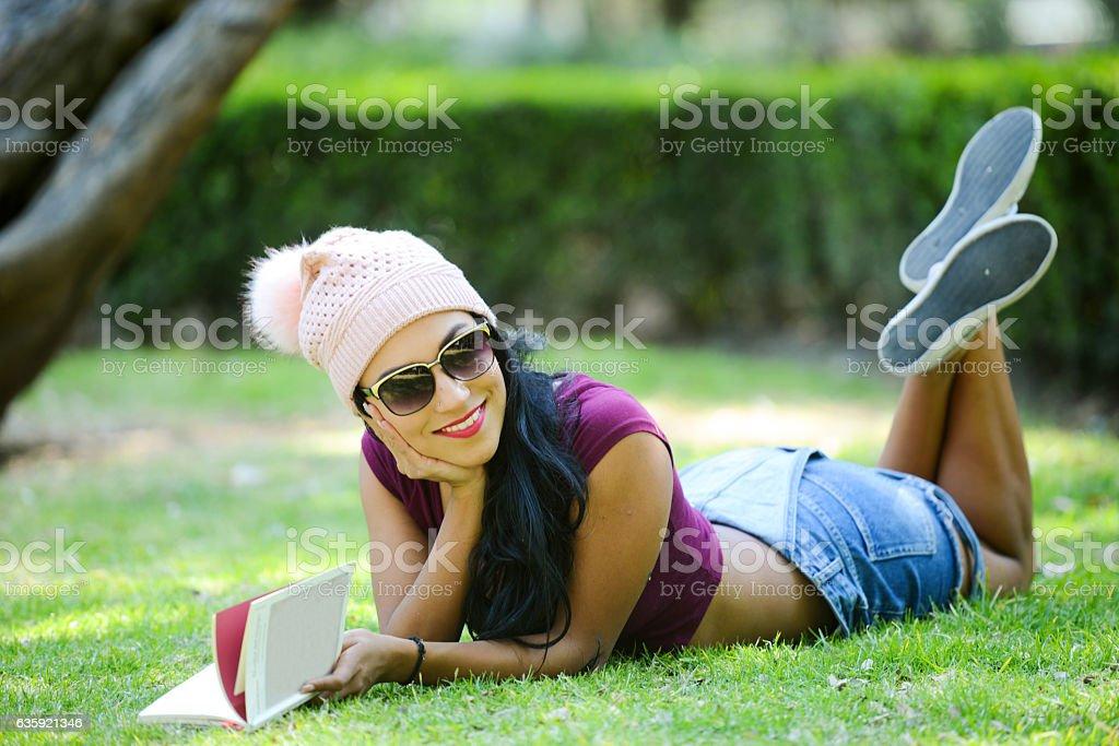 Mujer leyendo en el parque stock photo