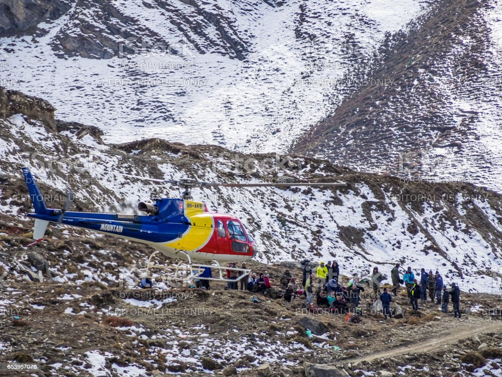 Muktinath, Nepal - March 17,2014: A multi-colored helicopter lands near the rescued tourists. In the helicopter are a few saved people. stock photo