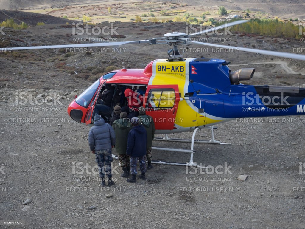 Muktinath, Nepal - March 17,2014: A multi-colored helicopter stands on the landing pad. From the helicopter comes the rescued tourist in a red jacket. Near the helicopter are soldiers of the army of Nepal, who take part in the operation for the rescue stock photo