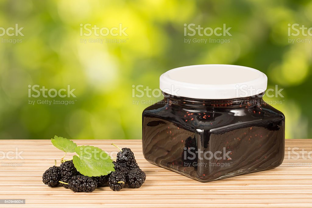 mulberry jam in jar and fresh fruits on table stock photo
