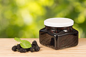 mulberry jam in jar and fresh fruits on table