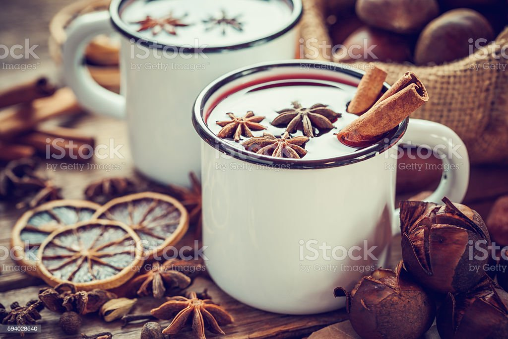 Mulled wine in mugs, dry fruits and chestnuts stock photo