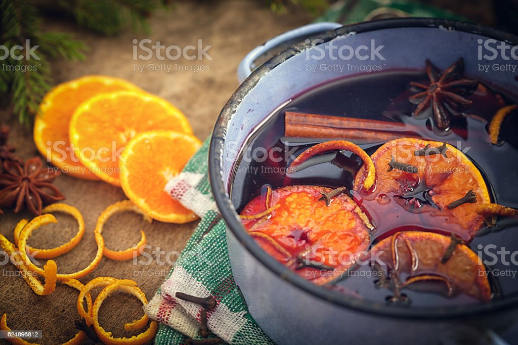 Mulled wine with spices and ingredients on wooden background stock photo