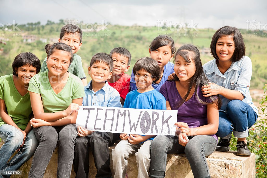 Mult-ethnic, large group of children hold 'teamwork' sign outdoors. stock photo