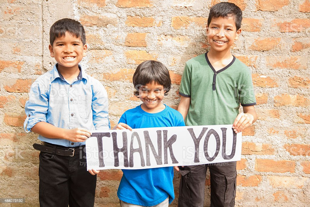 Mult-ethnic, small group of children hold 'Thank You' sign outdoors. stock photo