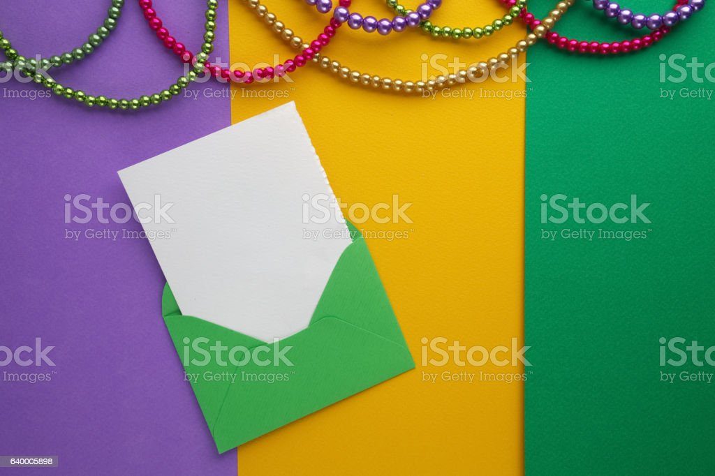 Multi color Mardi Gras beads and envelop with card on stock photo