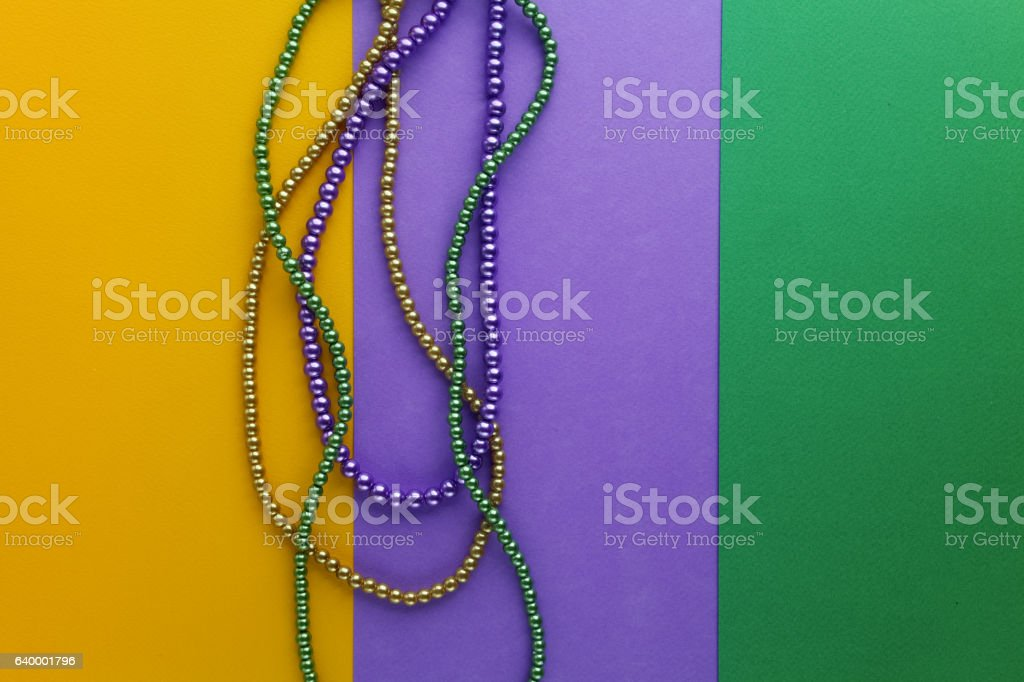 Multi color Mardi Gras beads on paper background. Top view stock photo