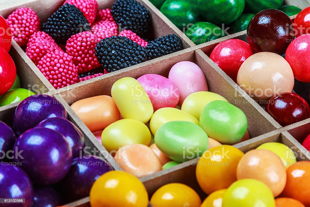 multi colored candy and chewing gum in a wooden box stock photo