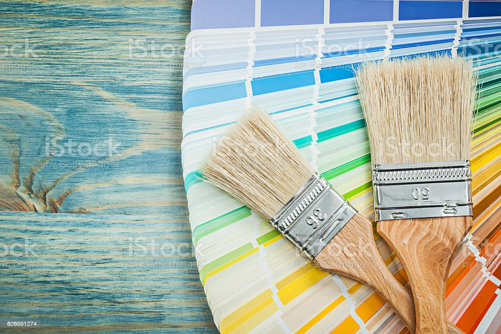 Multi colored color sampler paint brushes on wooden board constr stock photo