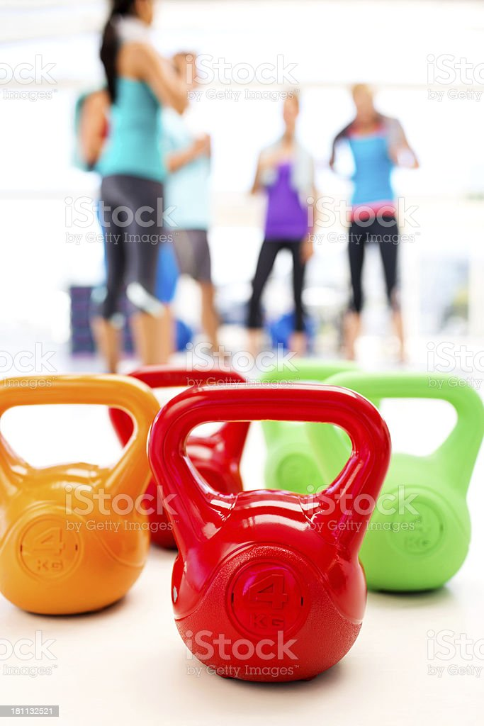 Multi Colored Kettle Bells With People In Background royalty-free stock photo