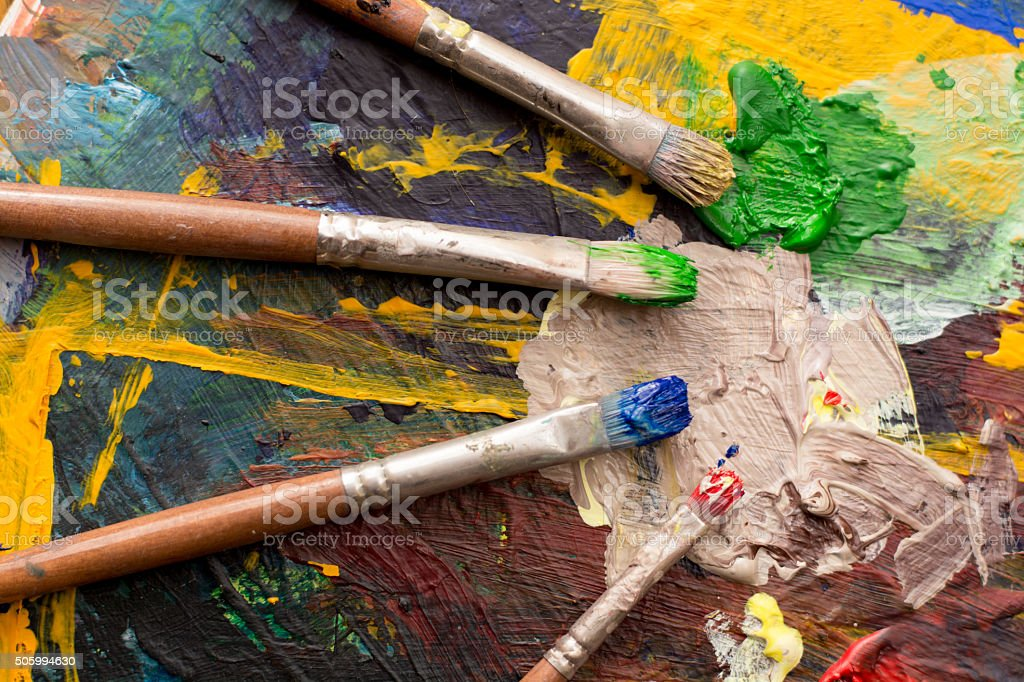 multi colored paint  palette and paintbrush stock photo