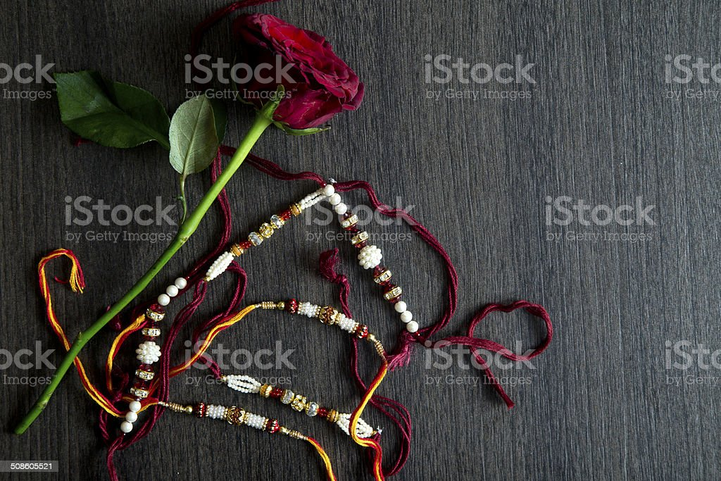 Multi colored Rakhi with red rose on wooden table stock photo