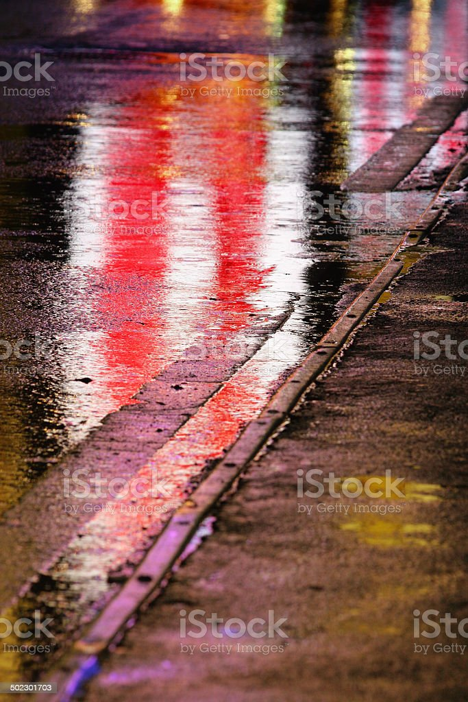 Multi colored street lights reflections on road asphalt, with curb...