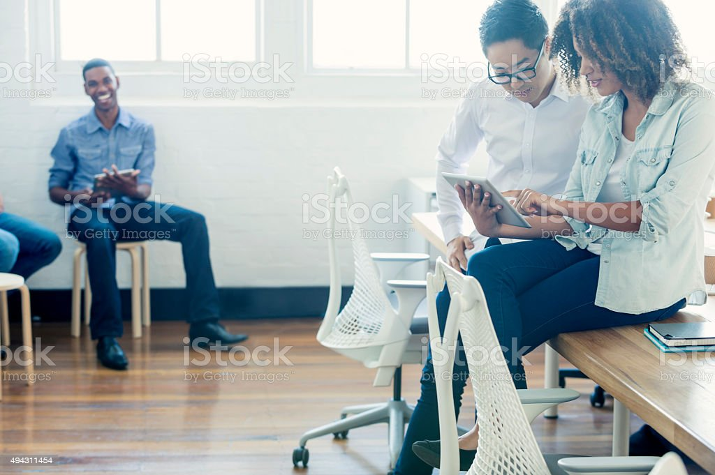 Multi cultural group working with technology. stock photo