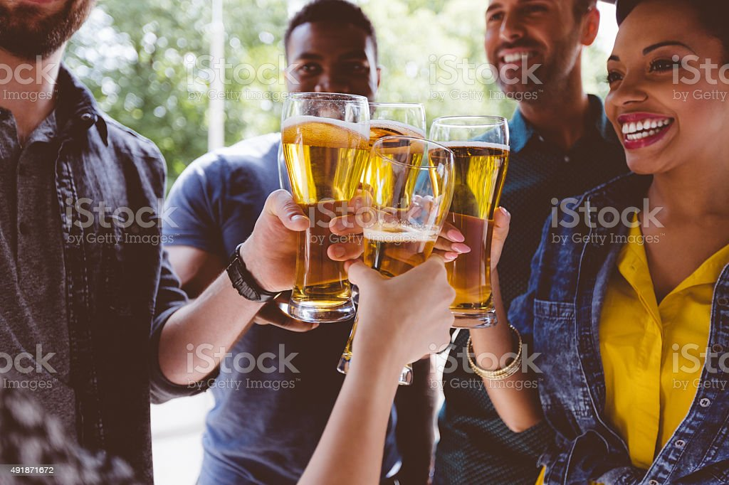 Multi ethinc friends toasting with beer outdoors stock photo