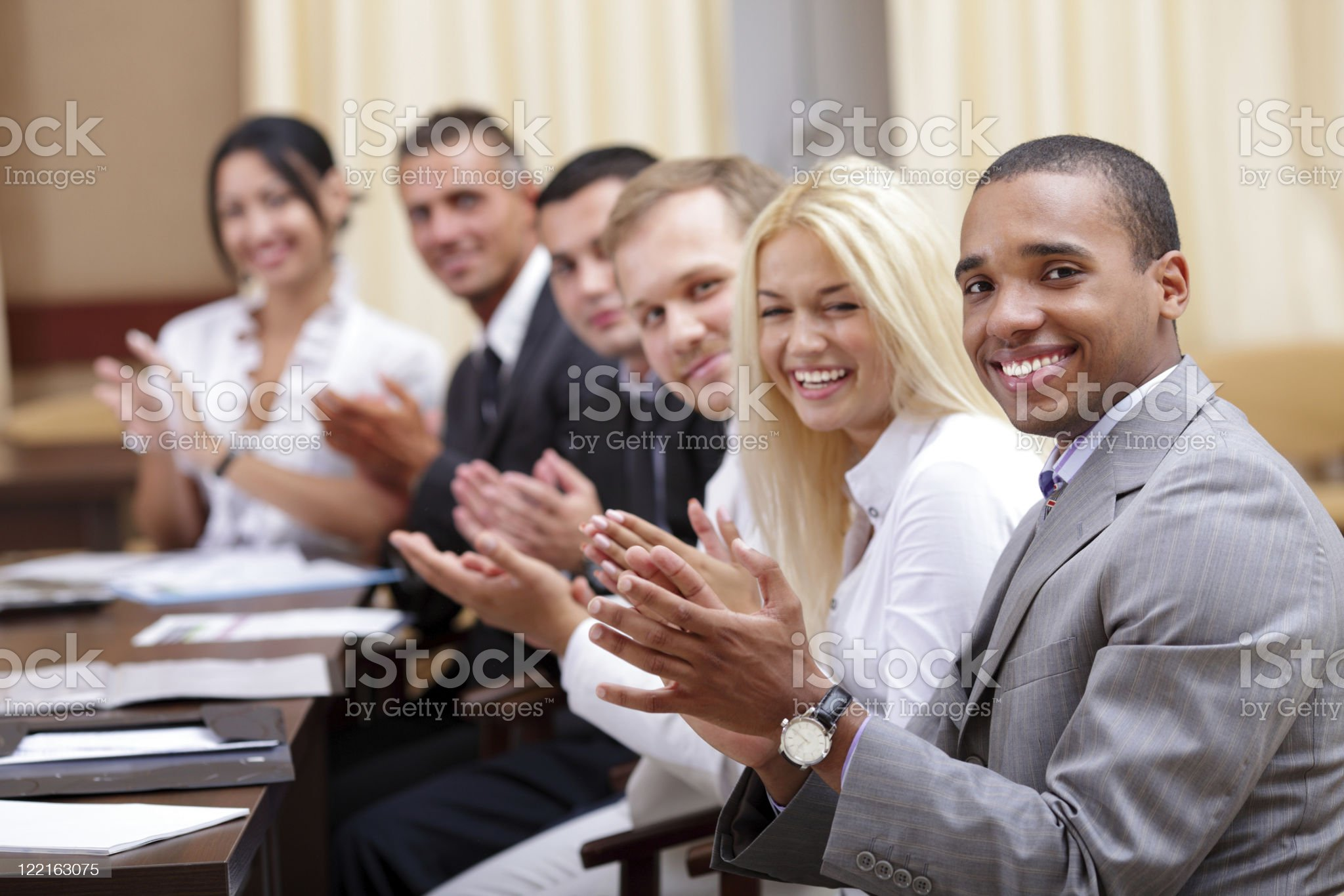 Multi ethnic business group greets you with clapping royalty-free stock photo