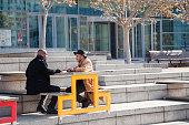 multi ethnic businessmen discuss in spring sunshine near office building