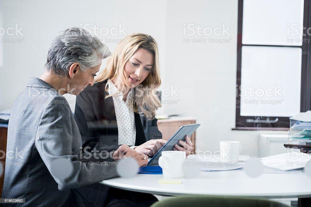 Multi ethnic businesswomen using tablet in modern office stock photo