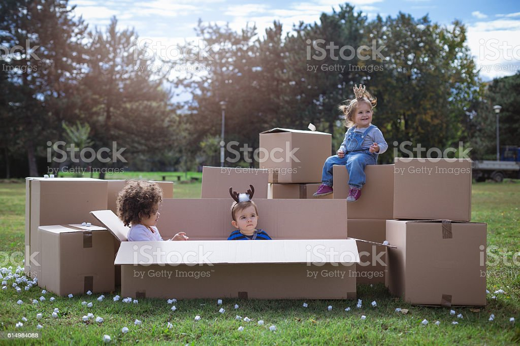 multi ethnic children playing with cardboard boxes stock photo
