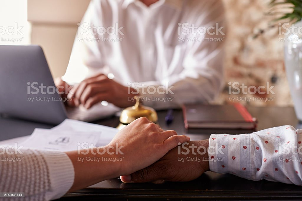 Multi ethnic couple hold hands at hotel check in desk stock photo