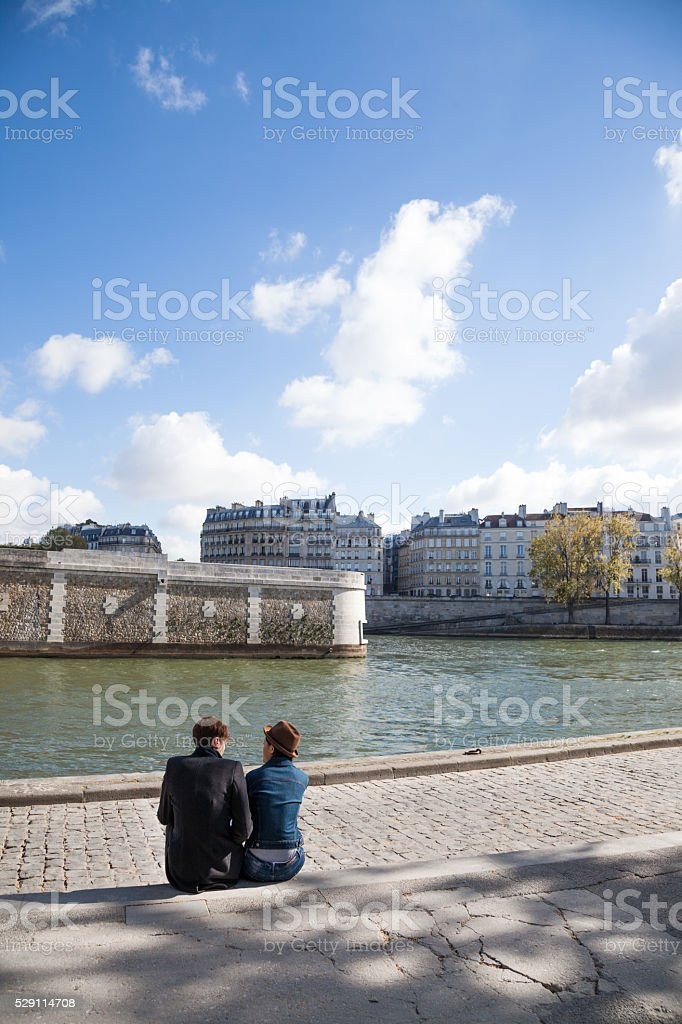 multi ethnic couple in love beside the Seine Paris stock photo