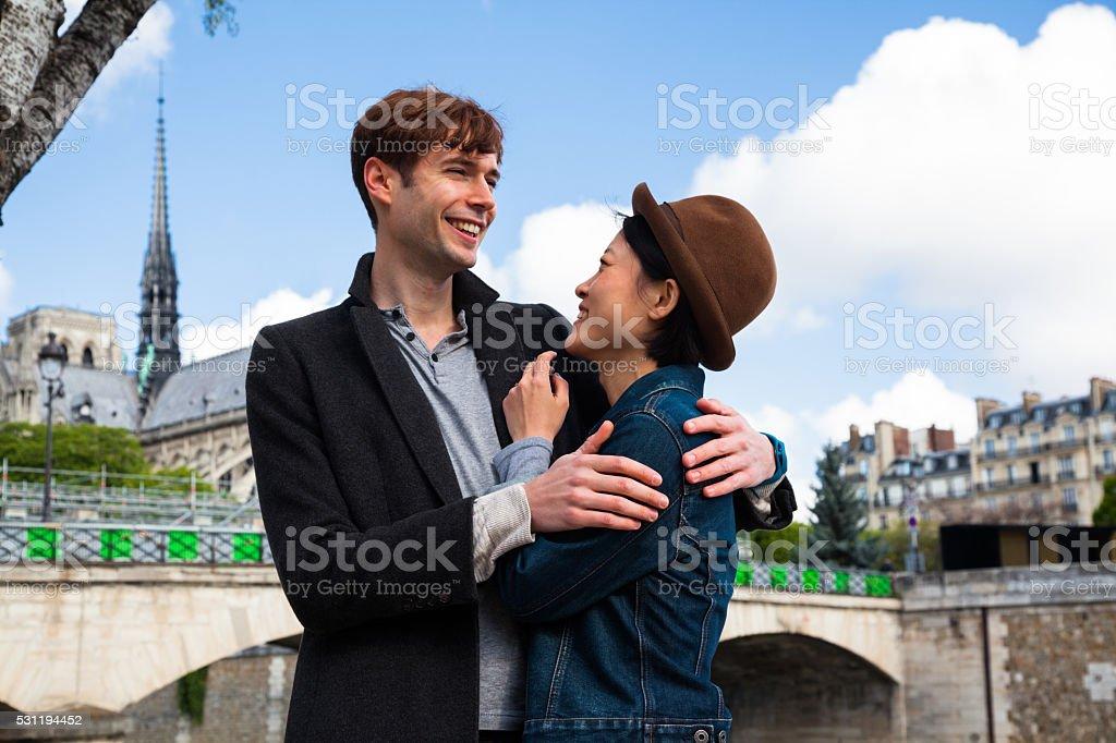 multi ethnic couple in love blue sky Notre dame paris stock photo