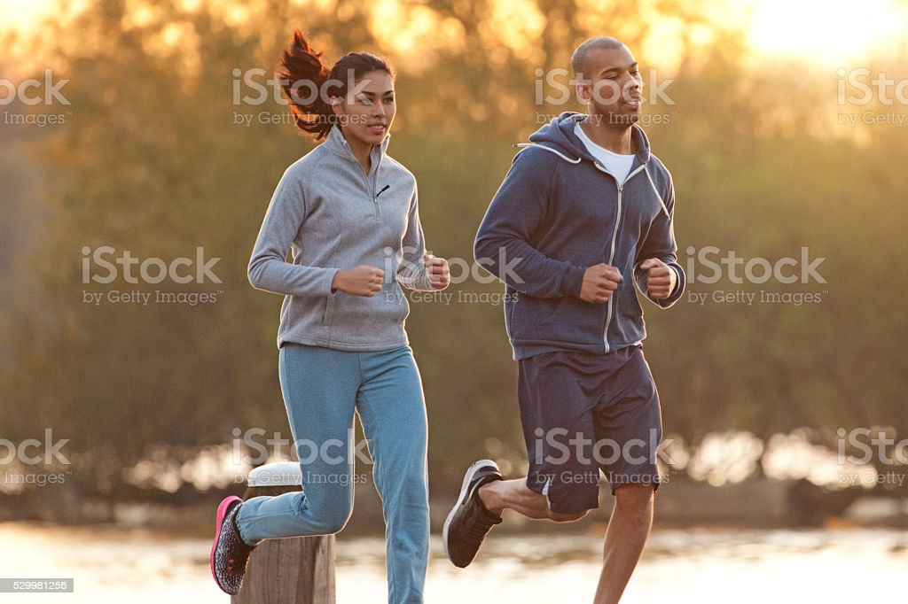 Multi ethnic couple running during a morning workout stock photo