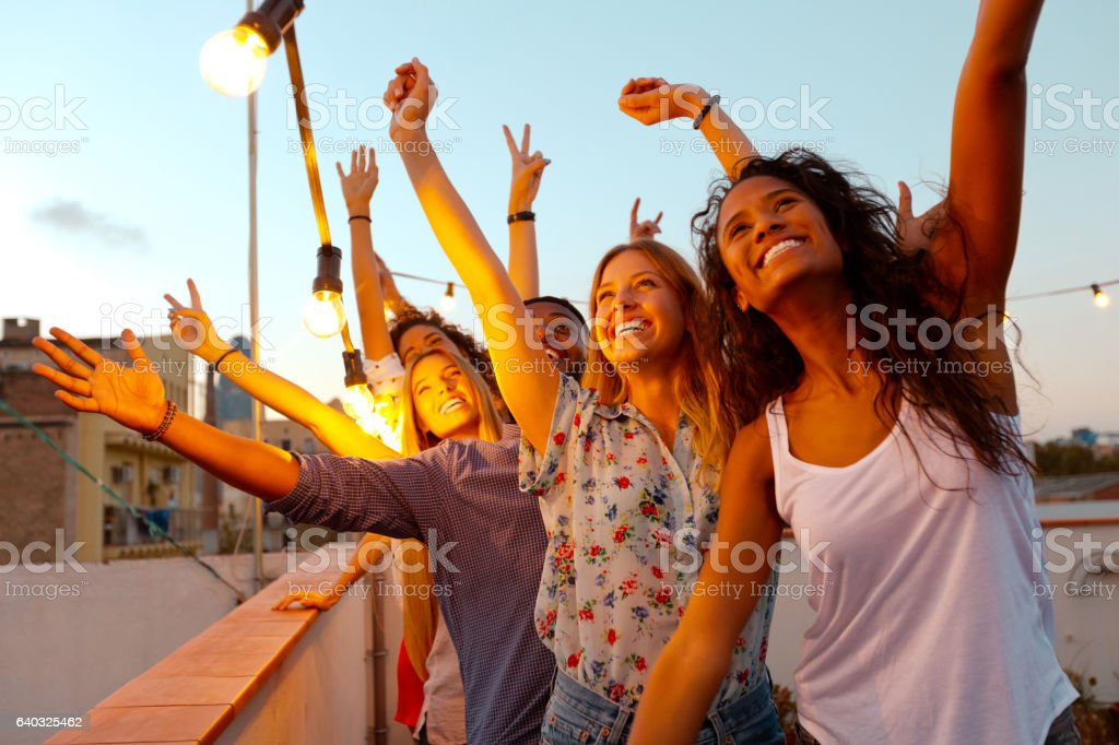 Multi ethnic friends dancing at the rooftop party stock photo