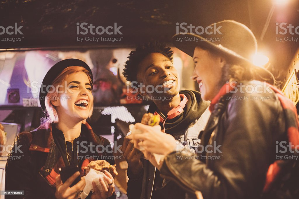 Multi ethnic friends eating burgers in pub stock photo