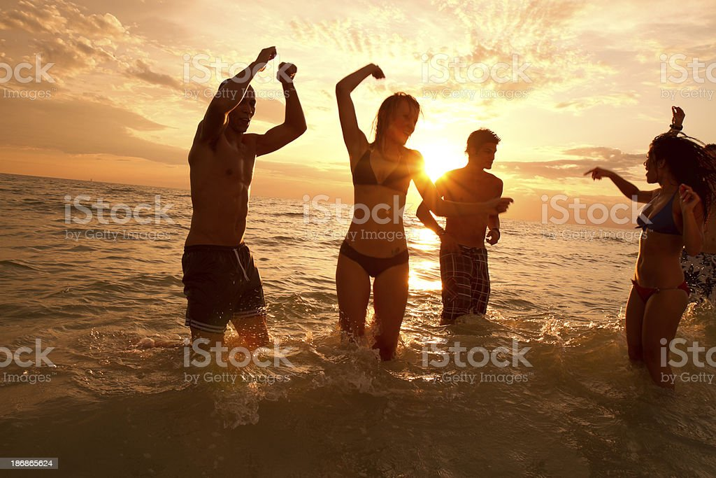 Multi ethnic friends having fun at the beach royalty-free stock photo