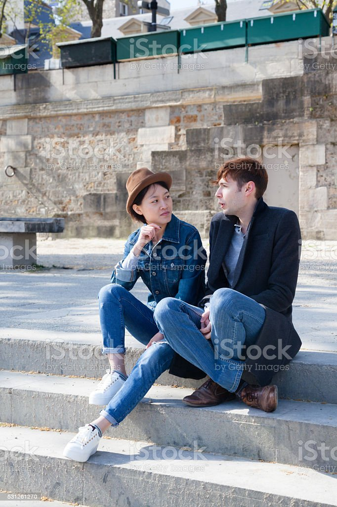 multi ethnic friends in conversation on the banks Seine Paris stock photo
