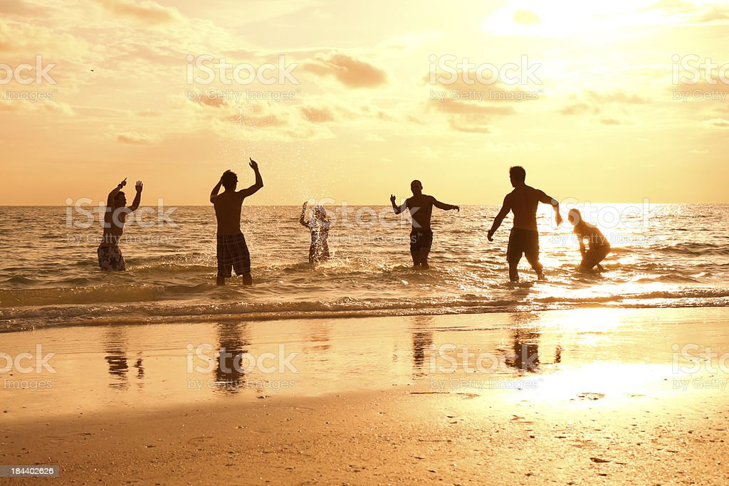 Multi ethnic friends playing on the beach royalty-free stock photo