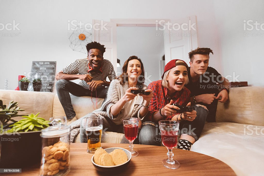 Multi ethnic friends playing video games at home stock photo