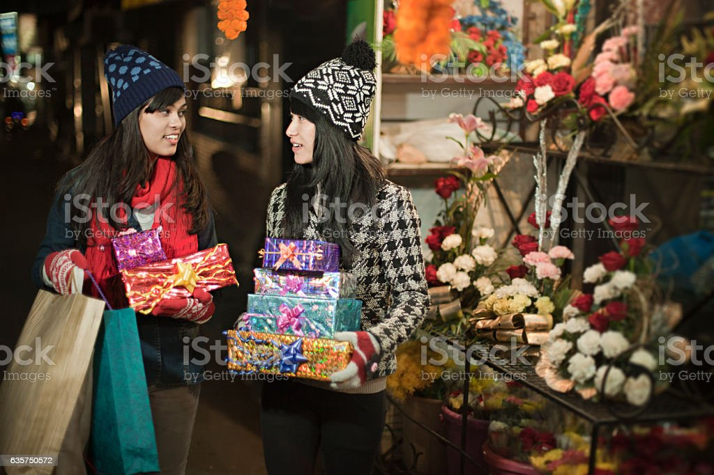 Multi ethnic girls in market carrying gifts and shopping bags. stock photo