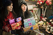 Multi ethnic girls in market carrying gifts and shopping bags.