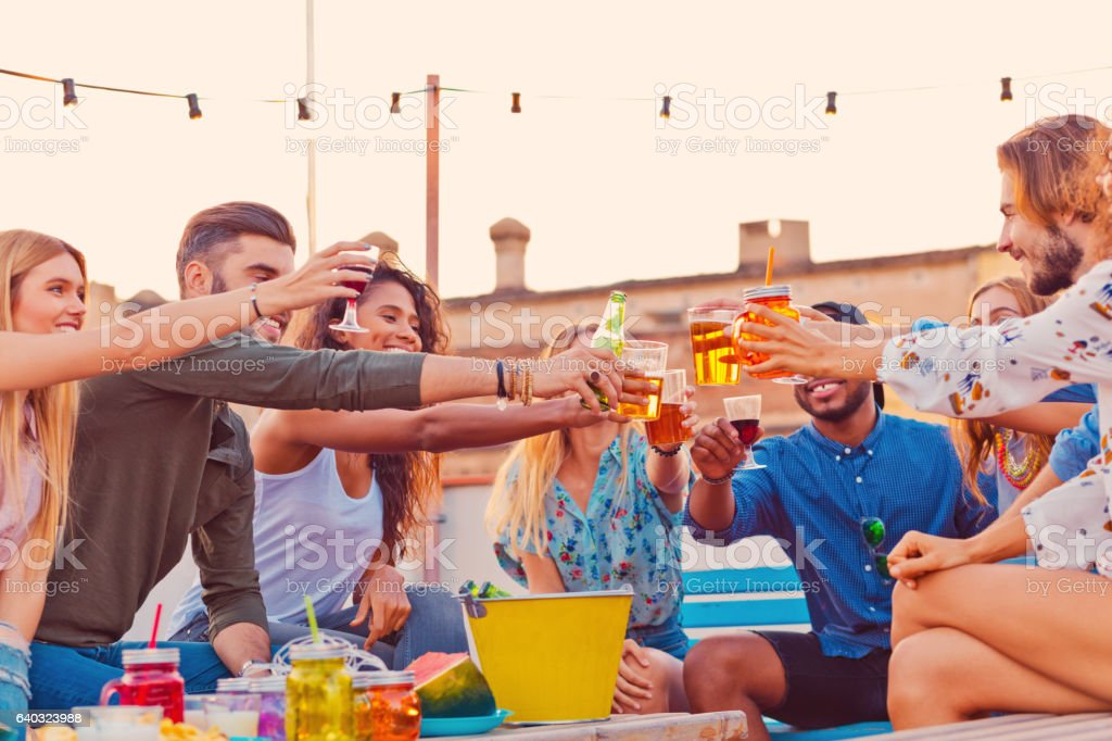 Multi ethnic group of friends at the rooftop party stock photo