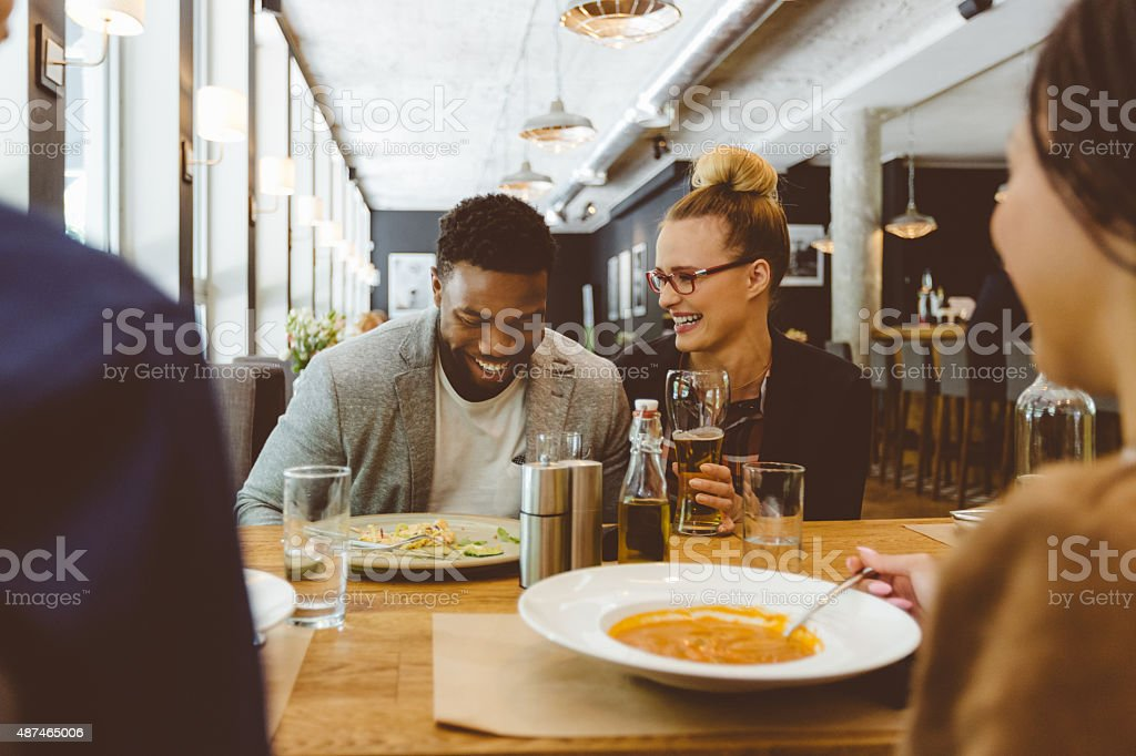 Multi ethnic group of friends eating dinner in a restaurant stock photo