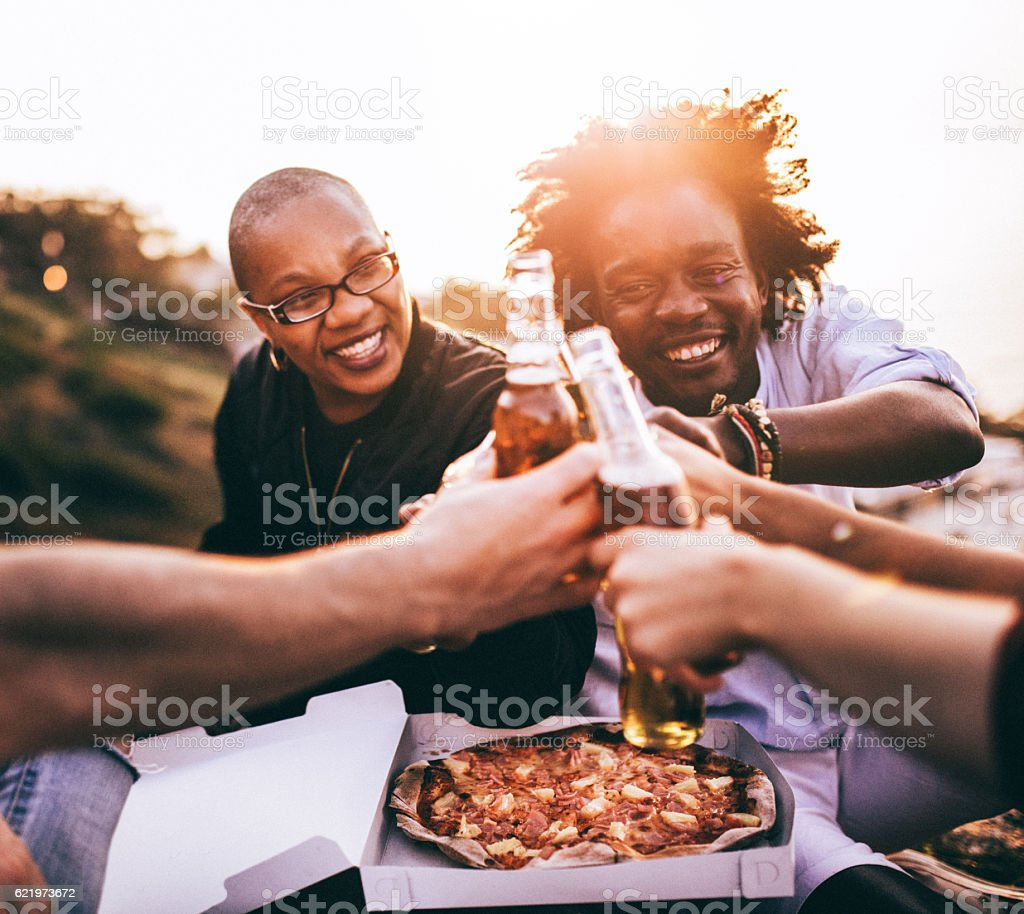 Multi Ethnic Group of friends enjoying drinks and pizza stock photo