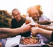 Multi Ethnic Group of friends enjoying drinks and pizza